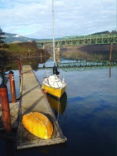 The yellow boat, the rusty dock stanchions, and the green bridge with grey cloud and blue sky reflections.